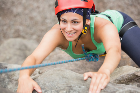 Happy girl climbing rock face wearing red helmet photo