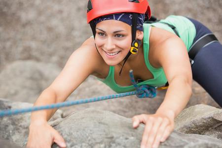 Happy girl climbing rock face wearing red helmet