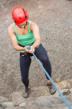 Sporty girl abseiling down rock face wearing red helmet photo
