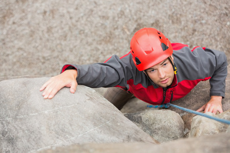 Determined man climbing rock face wearing red helmet photo