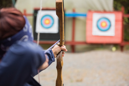 Brunette about to shoot arrow at the archery range photo