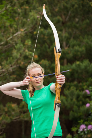 concentrating: Concentrating blonde woman practicing archery in the countryside
