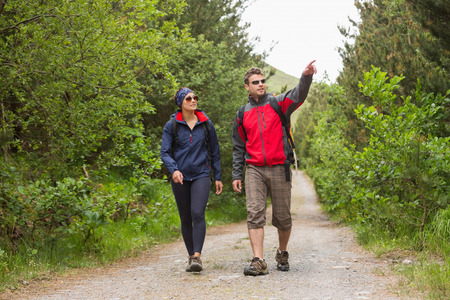 Couple going on a hike together with man pointing on a country trail photo