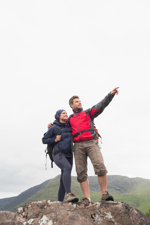 Couple standing on a rock looking up at the mountains on a hiking trip photo