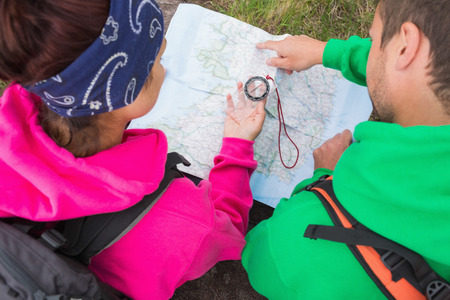 adventuring: Couple using compass and map on their hike in the country Stock Photo