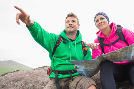 Couple using map and compass sitting on a rock with man pointing in the countryside photo