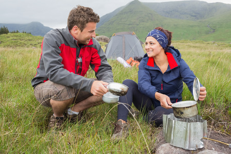 Couple cooking outside on camping trip and smiling in the countryside photo