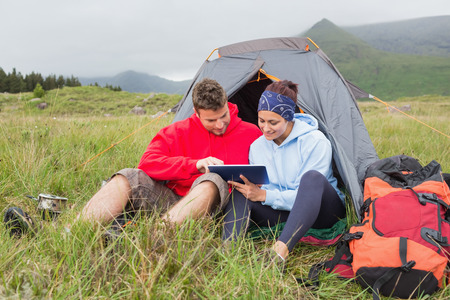 Couple on camping trip using a digital tablet outside their tent photo