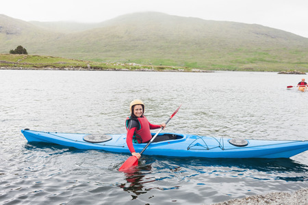 Smiling woman in a kayak in a lake looking at camera photo