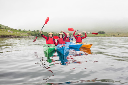 Fit friends rowing on a lake in kayaks and cheering at camera photo