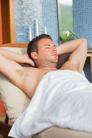 recliner: Man relaxing at the spa sitting in a recliner chair Stock Photo