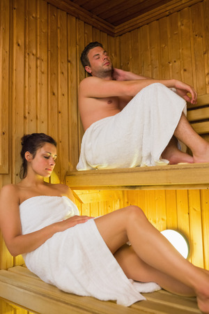 Content couple relaxing in a sauna wearing white towels photo