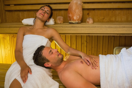 Loving couple relaxing in a sauna wearing white towels photo