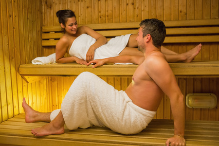 Calm couple relaxing in a sauna and chatting wearing white towels photo