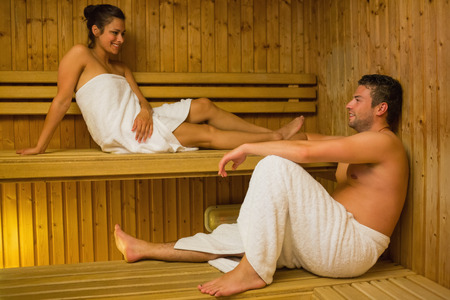 Happy couple relaxing in a sauna and chatting wearing white towels photo