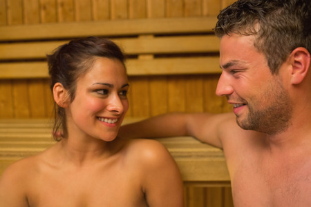 Cheerful couple relaxing in a sauna and chatting sitting on bench photo