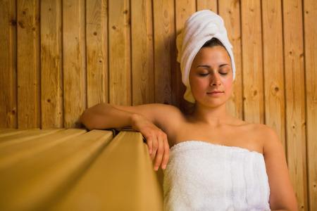 unwinding: Calm woman relaxing in a sauna wearing white towels