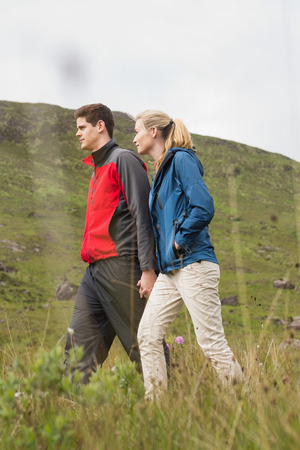 fit couple: Cheerful couple walking through the countryside wearing rain jackets