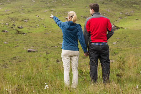 adventuring: Couple holding hands with woman pointing on a walk in the countryside
