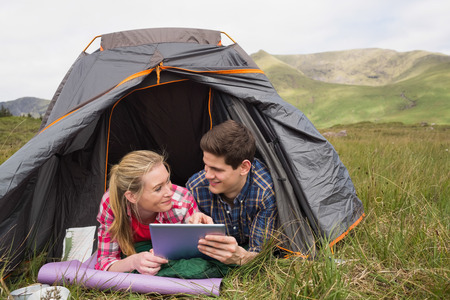 Happy couple lying in their tent and using digital tablet in the countryside photo