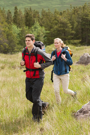 adventuring: Happy couple setting out on a hike in the countryside