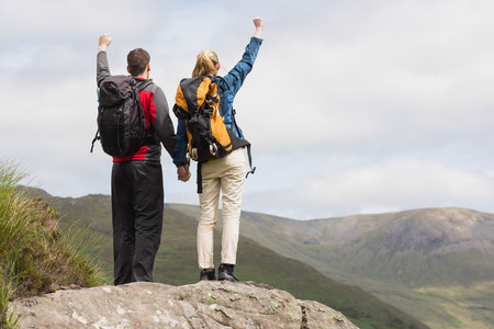 adventuring: Excited couple reaching the top of their hike and cheering in majestic mountain scenery