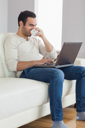 Relaxed attractive man drinking coffee while working on his laptop in bright living room photo