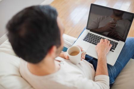 Hoge hoek oog van de jonge man met zijn laptop in lichte woonkamer