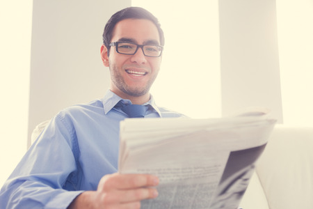 Happy man with glasses looking at camera and holding a newspaper photo