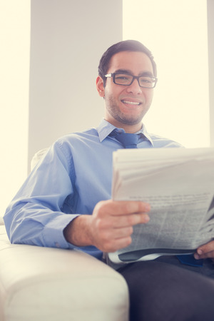 Content man with glasses looking at camera and holding a newspaper sitting on a sofa photo