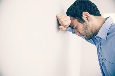 desolaci�n: Hombre deprimido con el pu�o cerrado apoyando su cabeza contra una pared