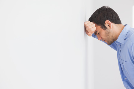 restless: Angry man with fist clenched leaning his head against a wall
