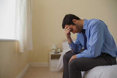 mournful: Mournful man sitting head in hands on his bed in a bedroom at home Stock Photo