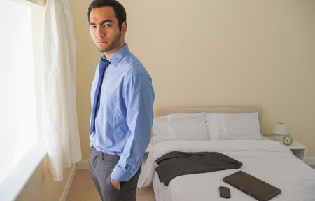 Irritated man looking at camera standing in front of a window in a bedroom at home photo