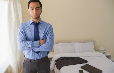 Serious man looking at camera and standing with crossed arms in a bedroom at home photo