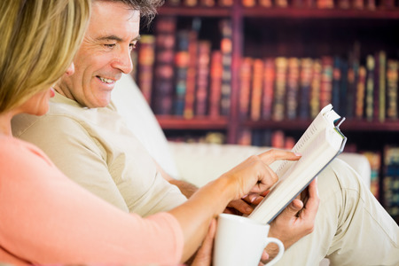 Happy mature couple reading a book in a reading room and drinking coffee photo