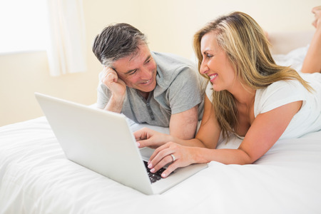 Laughing mature couple lying on a bed in a bedroom using a laptop photo
