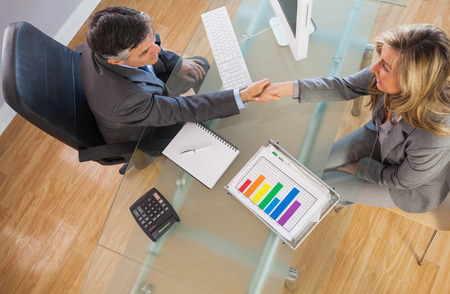 person woman: A businessman shaking the hand of a businesswoman above a desk in an office