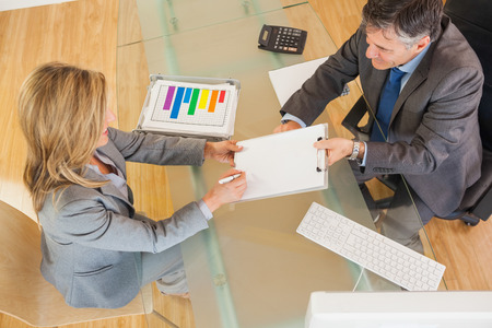 A businessman making a businesswoman signing a contract in an office above a desk photo