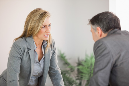 A blonde businesswoman getting angry with a businessman photo