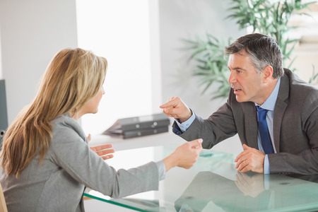 A blonde businesswoman and a mature businessman having an argument in an office photo