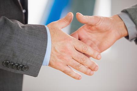 estrechando manos: Dos hombres de negocios a punto de darle la mano en una oficina Foto de archivo