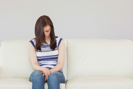 wistfulness: Depressed brunette sitting idly on a sofa looking the floor Stock Photo