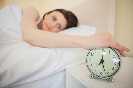 obudził: Awakened brunette turning off her alarm clock in her bedroom Zdjęcie Seryjne
