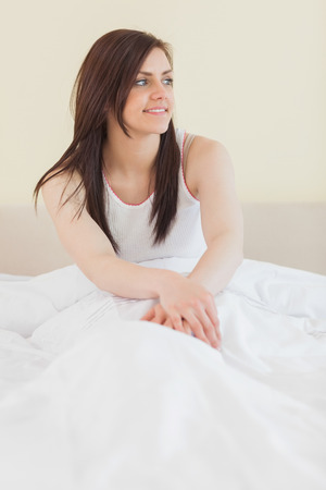 obudził: Awakened brunette looking away and sitting in her bed on yellow background Zdjęcie Seryjne