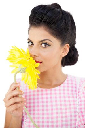 Seductive black hair model smelling a flower on white background photo
