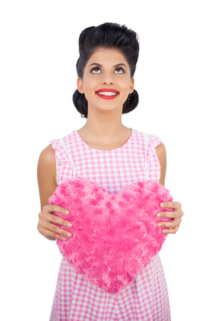 Content black hair model holding a pink heart shaped pillow on white background photo