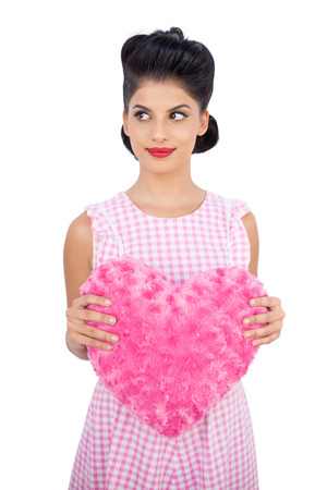 Pretty black hair model holding a pink heart shaped pillow on white background photo