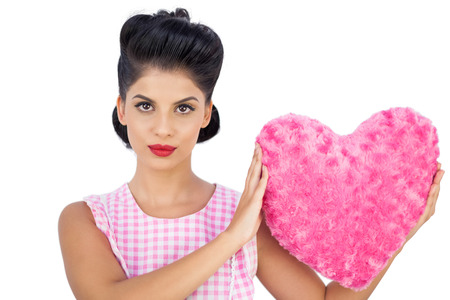 Unsmiling black hair model holding a pink heart shaped pillow on white background photo