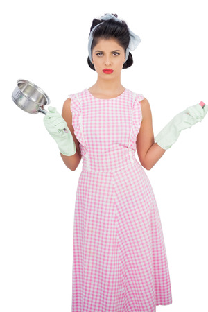 Disppointed black hair model holding a pan and wearing rubber gloves on white background  photo